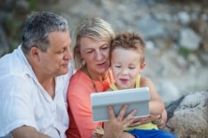 grandparents with grandson and ipad